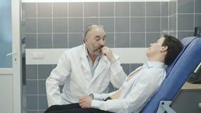 Ciérrese encima del retrato del doctor que consulta al paciente 4K almacen de metraje de vídeo