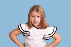 Ciérrese encima del retrato emocional de la muchacha rubia joven en fondo azul en estudio E imágenes de archivo libres de regalías