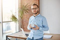 Ciérrese encima del retrato del fundador atractivo joven de la compañía en vidrios y equipo casual, colocándose en la oficina per imagen de archivo libre de regalías