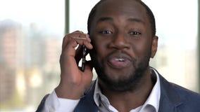 Ciérrese encima del retrato del hombre africano que habla en el teléfono almacen de video