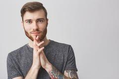 Ciérrese encima del retrato del hombre caucásico feliz hermoso con la barba, el peinado de moda y el brazo tatuado llevando la ca Imagen de archivo libre de regalías