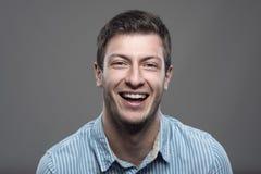 Ciérrese encima del retrato horizontal cambiante de la risa acertada joven del hombre Imagen de archivo libre de regalías