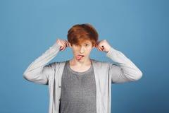 Ciérrese encima del retrato del individuo joven apuesto del jengibre en el equipo gris casual que sostiene los oídos con las mano Fotografía de archivo