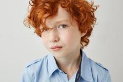 Ciérrese encima del retrato del niño hermoso con los ojos rojos del pelo rizado y del gris que miran in camera con serio y relaja Foto de archivo libre de regalías