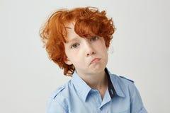 Ciérrese encima del retrato del niño pequeño divertido con el pelo rizado rojo y las pecas que miran in camera con la expresión i Fotografía de archivo