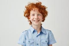 Ciérrese encima del retrato del niño pequeño divertido con el pelo y las pecas anaranjados que siega ojos, sonriendo y haciendo l Imágenes de archivo libres de regalías