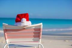 Ciérrese encima del sombrero de Papá Noel en longue de la silla en tropical Foto de archivo