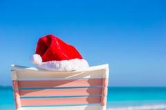 Ciérrese encima del sombrero de Papá Noel en longue de la silla en tropical Imagen de archivo