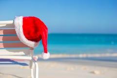 Ciérrese encima del sombrero de Papá Noel en longue de la silla en tropical Foto de archivo libre de regalías