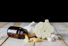 Ciérrese encima del suplemento del gel de la cápsula del ajo y del aceite en el CCB de madera del blanco imagenes de archivo