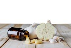 Ciérrese encima del suplemento del gel de la cápsula del ajo y del aceite en el CCB de madera del blanco foto de archivo