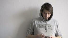 Ciérrese encima del teléfono joven hermoso de Guy Busy With His Mobile, aislado en gris almacen de video