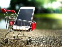 Ciérrese encima del teléfono móvil en el carro de la compra, negocio en concepto del comercio electrónico Imágenes de archivo libres de regalías