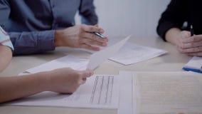 Ciérrese encima del tiro del agente de la propiedad inmobiliaria que muestra el contrato para la casa de compra a la pareja casad metrajes