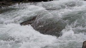 Ciérrese encima del tiro del agua El agua de los flujos de corriente con las rocas en la cámara lenta almacen de video