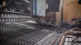 Ciérrese encima del tiro de la mano de la persona, que está funcionando en crear una electro melodía en el estudio de grabación d almacen de video