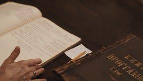 Ciérrese encima del tiro de la mujer mayor que las manos hojean a través del texto cursivo ruso del libro en la tabla almacen de metraje de vídeo