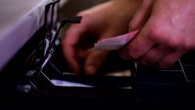 Ciérrese encima del tiro de las manos masculinas del cajero que ponen el dinero que cuenta billetes de banco en cajón abierto del metrajes