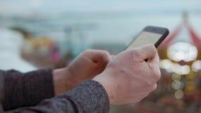 Ciérrese encima del tiro de las manos del ` s del hombre, él que hojea la previsión metereológica en el smartphone almacen de video