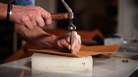 Ciérrese encima del tiro de las manos del ` un s del empleado, que hace los agujeros con un martillo en un eather metrajes