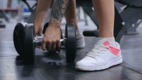 Ciérrese encima del tiro de las pesas de gimnasia de elevación atléticas de la mujer joven en el gimnasio almacen de metraje de vídeo