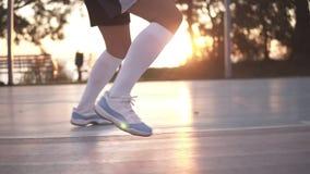 Ciérrese encima del tiro de las piernas femeninas del jugador de básquet que hacen exersice de goteo muy rápidamente sin la bola, metrajes