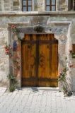 ciérrese encima del tiro de las puertas de madera viejas rodeadas por las flores, imágenes de archivo libres de regalías