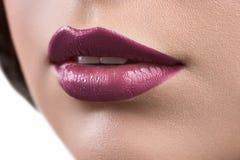 Ciérrese encima del tiro de los labios de un glo del lápiz labial o del labio de la mujer que lleva Foto de archivo