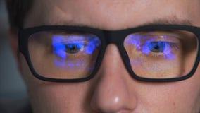 Ciérrese encima del tiro de los ojos de un hombre en vidrios que esté mirando una película metrajes