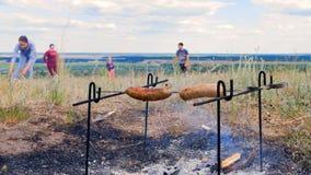Ciérrese encima del tiro de quién se fríen las salchichas de la carne del cocinero, ellas en el fuego en un prado en un día de ve almacen de metraje de vídeo