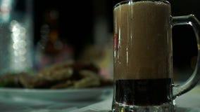 Ciérrese encima del tiro de verter la cerveza oscura con mucha espuma en la taza de cristal grande metrajes