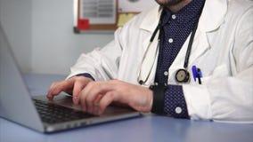 Ciérrese encima del tiro del doctor que trabaja usando el ordenador portátil almacen de metraje de vídeo
