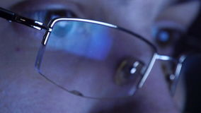 Ciérrese encima del tiro del hombre en los vidrios que practican surf Internet en la noche almacen de video