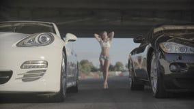Ciérrese encima del tiro del nuevo deporte dos que compite con los coches modernos listos para comenzar con la mujer atractiva ap almacen de video