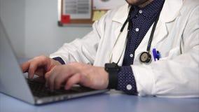 Ciérrese encima del tiro del trabajador médico que trabaja usando el ordenador portátil almacen de video