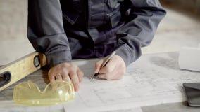 Ciérrese encima del tiro en de las manos del ` s del hombre, que hace notas en el dibujo de construcción para el capataz y los co almacen de metraje de vídeo