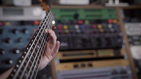 Ciérrese encima del tiro del músico ambicioso que sostiene una guitarra baja en sus manos almacen de metraje de vídeo