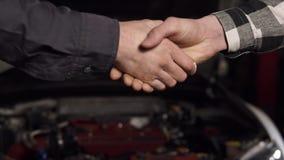 Ciérrese encima del tiro del mecánico y del cliente que sacuden las manos en un taller de reparaciones auto almacen de metraje de vídeo
