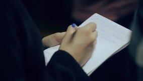 Ciérrese encima del tiroteo de la hembra de las manos Niza que toma notas en cuaderno almacen de video