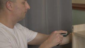 Ciérrese encima del tornillo apretado del carpintero de sexo masculino de la mano por el destornillador eléctrico que trabaja en  almacen de metraje de vídeo