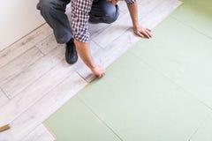 Ciérrese encima del trabajador del carpintero de las manos del hombre que instala el suelo laminado en el nuevo cuarto fotos de archivo libres de regalías