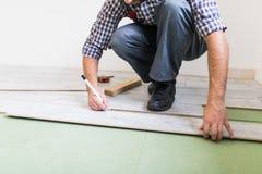 Ciérrese encima del trabajador de las manos del hombre que instala el suelo laminado en el nuevo cuarto imágenes de archivo libres de regalías