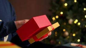 Ciérrese encima del varón da un regalo Los pares atractivos jovenes en el sombrero de Papá Noel, suéteres acogedores, sonriendo,  almacen de metraje de vídeo