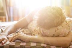 Ciérrese encima del varón joven que miente en sueño de la cama en mroning contra el throung de la sol la ventana f fotos de archivo libres de regalías