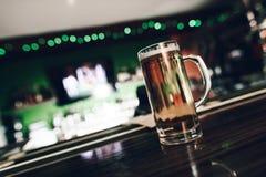 Ciérrese encima del vidrio de cerveza que se coloca en la tabla de la barra en la barra de deportes foto de archivo
