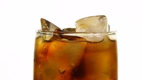 Ciérrese encima del vidrio de cola con los cubos de hielo en blanco metrajes