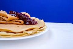 Ciérrese encima del vidrio ruso del witg de las crepes del blini de la leche y de las fresas est en fondo azul Foodphotography fotografía de archivo