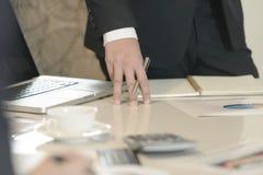 Ciérrese hasta la mano del hombre de negocios en la mesa de reuniones, negocio Foto de archivo