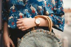 Ciérrese para arriba, blogger de la moda que lleva una camisa del verano y un reloj análogo blanco y marrón, sosteniendo un moned imagen de archivo libre de regalías