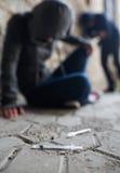 Ciérrese para arriba de adictos y de jeringuillas de la droga en la tierra Foto de archivo